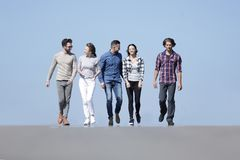 Equipe dos jovens que andam ao longo da estrada outdoors foto de stock