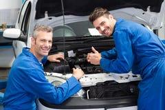 Equipe dos mecânicos que trabalham junto Fotos de Stock