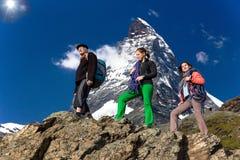 A equipe dos montanhistas anda contra o fundo alpino Fotografia de Stock