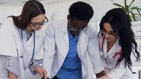 Equipe dos multi doutores nacionais que discutem o resultado da análise do sangue na sala de conferências do hospital video estoque