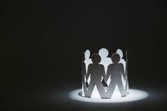 Equipe dos povos de papel da boneca que guardam as mãos na luz Fotografia de Stock