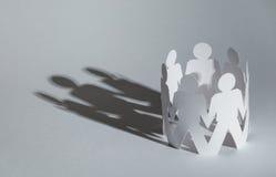 Equipe dos povos de papel da boneca que guardaram as mãos Imagem de Stock Royalty Free