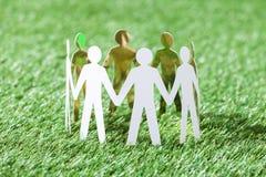 Equipe dos povos de papel no campo gramíneo Fotografia de Stock Royalty Free