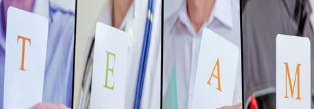 Equipe dos povos de Profesional que mostra o cartão com letras fotografia de stock