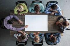 Equipe dos povos em torno do papel vazio fotografia de stock