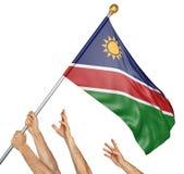 A equipe dos povos entrega o levantamento da Namíbia bandeira nacional fotos de stock