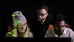 Equipe dos profissionais de TI multi-étnicos que trabalham com os computadores em escuro, cortando o sistema informático filme
