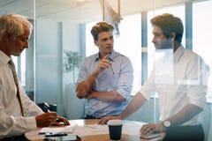 Equipe dos profissionais incorporados que encontram-se em torno de uma tabela Fotografia de Stock Royalty Free