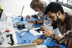 Equipe dos técnicos da eletrônica que trabalha nas peças do computador imagem de stock