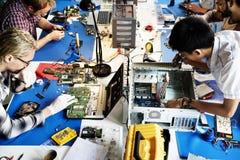 Equipe dos técnicos da eletrônica que trabalha nas peças do computador foto de stock