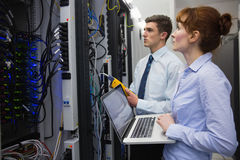 Equipe dos técnicos que usam o analisador digital do cabo em servidores Foto de Stock Royalty Free