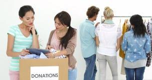 Equipe dos trabalhadores de sorriso que usam a tabuleta ao lado da caixa da doação