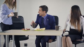 Equipe dos trabalhadores que situam na tabela durante o almoço dentro do escritório vídeos de arquivo