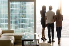 Equipe e duas mulheres que olham para fora a janela, vista traseira Foto de Stock Royalty Free