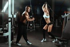 Equipe e os músculos treinados uma mulher no gym fotografia de stock