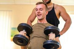 Equipe e seu instrutor pessoal que exercita com pesos no Gym Exercícios da técnica para os ombros atleta do principiante com coac Fotografia de Stock