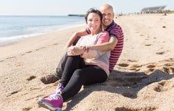 Equipe e uma mulher de meia idade que senta-se na praia imagens de stock
