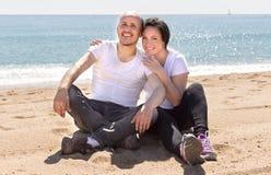 Equipe e uma mulher de meia idade que senta-se na praia fotografia de stock royalty free