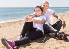 Equipe e uma mulher de meia idade que senta-se na praia foto de stock