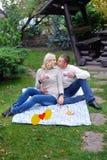 Equipe e uma mulher que senta-se em uma cama no parque que tem um piquenique Imagens de Stock