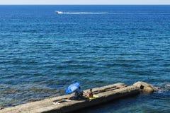 Equipe e uma mulher que senta-se em uma parede de pedra no mar imagens de stock royalty free