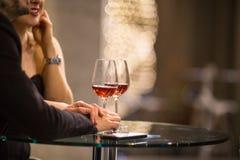 Equipe e uma mulher que tem bebidas/vidro do vinho em uma barra imagem de stock royalty free