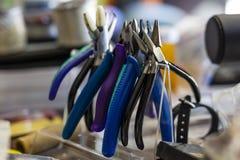 Equipe el estante para los arrugadores de los alicates y otras herramientas de la mano para la joyería c fotografía de archivo libre de regalías
