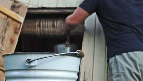 Equipe a elaboração da água fresca de um poço e o derramamento dela em uma cubeta no campo video estoque