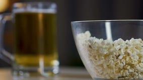 Equipe em casa comer a pipoca e beber a cerveja que aprecia filmes favoritos na tevê vídeos de arquivo