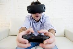 Equipe em casa o jogo de utilização entusiasmado dos óculos de proteção 3d do sofá do sofá da sala de visitas Imagens de Stock Royalty Free