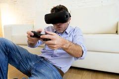 Equipe em casa o jogo de utilização entusiasmado dos óculos de proteção 3d do sofá do sofá da sala de visitas Fotografia de Stock