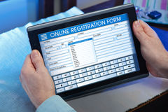 Equipe em casa a vista do formulário em linha vazio da avaliação na tabela digital Foto de Stock