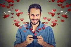 Equipe a emissão da mensagem dos sms do amor no telefone celular com os corações que voam afastado Fotografia de Stock Royalty Free