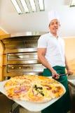 Equipe a empurrão da pizza terminada do forno Fotografia de Stock