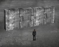 Equipe enfrentar quatro enigmas concretos enormes conectados junto Imagens de Stock Royalty Free