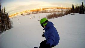 Equipe a equitação no snowboard com a vara do selfie em sua mão filme