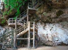 Equipe escadas feitas até a caverna no penhasco rochoso foto de stock royalty free