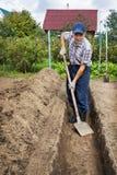 Equipe a escavação da terra para construir uma cama profunda de Foto de Stock Royalty Free
