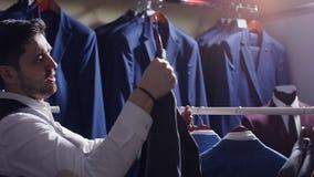 Equipe a escolha do terno de negócio na loja de roupa dos homens video estoque