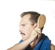 Equipe a escovadela de seu cabelo no espelho do banheiro. fotografia de stock