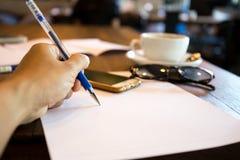 Equipe escrita canhota na nota com a pena no papel com phon da pilha foto de stock