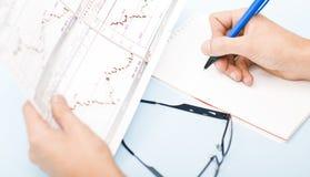 Equipe a escrita em gráficos da terra arrendada da agenda em sua mão Fotografia de Stock