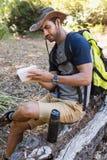 Equipe a escrita no bloco de notas ao descansar no tronco de árvore fotografia de stock royalty free