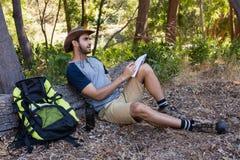 Equipe a escrita no bloco de notas ao descansar no tronco de árvore imagens de stock