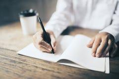 Equipe a escrita no diário vazio e no copo de café de papel na tabela de madeira Foto de Stock