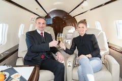 Equipe executiva do negócio em um jato incorporado que bebe um vidro de c Foto de Stock Royalty Free