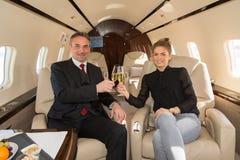 Equipe executiva do negócio em um jato incorporado que bebe um vidro de c Fotos de Stock Royalty Free