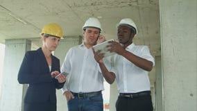 Equipe executiva no canteiro de obras que revê com tabuleta, smartphone, pessoa vestido formal que lê a tabuleta da construção filme