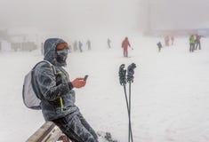 Equipe exterior ereto na neve e na névoa e no texting no smartpho foto de stock
