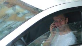 Equipe a fala em um telefone celular ao sentar-se no carro Excitador de sorriso filme